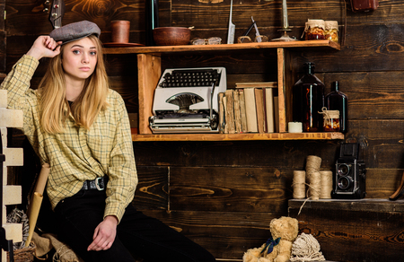 Tomboy concept. Girl tomboy spend time in house of gamekeeper. Girl in casual outfit with kepi in wooden vintage interior. Lady on calm face in plaid clothes looks cute and casual