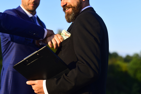Man with beard and smiling face holds folder takes bribe. Stock Photo