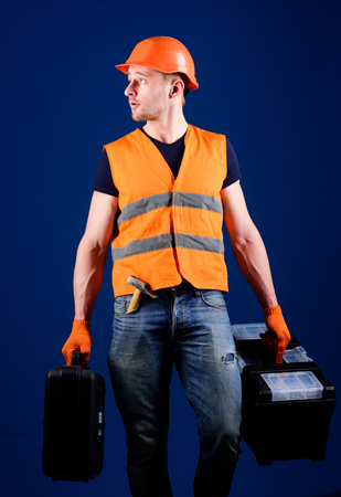 Professional repairman concept. Man in helmet, hard hat holds toolbox and suitcase with tools, blue background. Handyman, repairman on concentrated face carries heavy bags with professional equipment