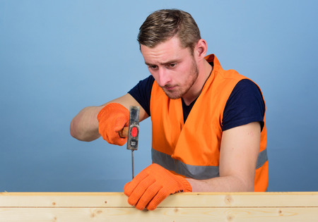 Man, handyman in working uniform and protective gloves handcrafting, light blue background. Carpenter, woodworker, builder on concentrated face hammering nail into wooden board. Carpenter concept