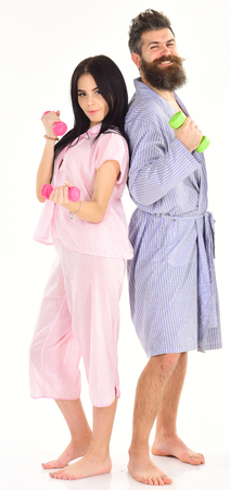 Couple, family do sports in morning, full of energy. Girl and man with dumbbells, morning exercises. Couple in love in pajama, bathrobe stand isolated on white background. Sporty lifestyle concept