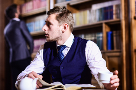 Young men with antique bookshelves on background. Stock Photo