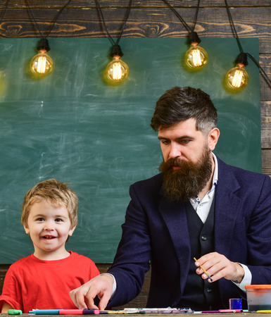 Dad and kid having fun at art class. Daddy and son painting together