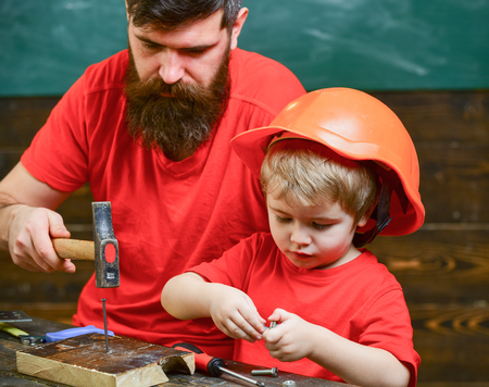 Father, parent with beard teaching little son to use hobnails and hammer. Boy, child busy in protective helmet learning to hammering hobnails with dad. Workshop and handyman concept