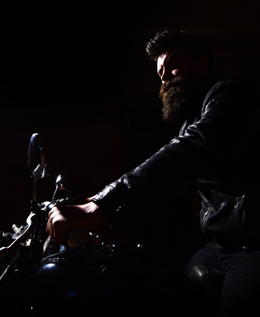 Hipster, brutal biker in leather jacket riding motorcycle at night time, copy space. Man with beard, biker in leather jacket sitting on motor bike in darkness, black background. Night rider concept