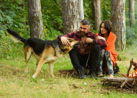 Couple with german shepherd dog sit near bonfire, forest background.