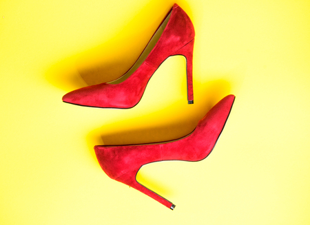 Feminine shoes concept. Footwear with thin high heels, stiletto shoes, top view. Shoes made out of red suede on yellow background. Pair of fashionable high heeled pump shoes