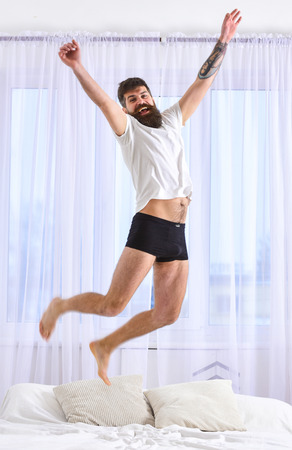 Man in shirt and underpants jumping on bed, white curtains on background. Guy on cheerful face full of energy in morning. Macho with beard jumps high in air. Full of strength and energy concept