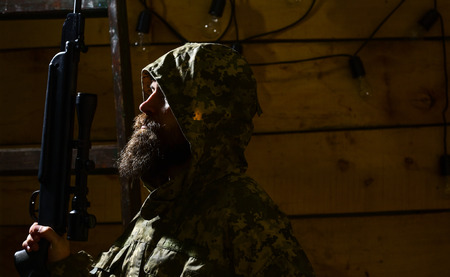 Man with beard wears camouflage hooded clothing, wooden interior background. Huntsman concept. Hunter, hipster with gun prepare rifle for hunting. Macho on strict face at gamekeepers house Stock fotó