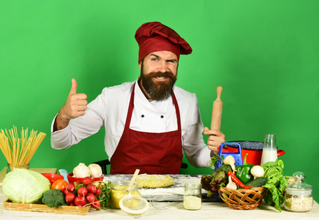 Man with beard sits by counter on green background