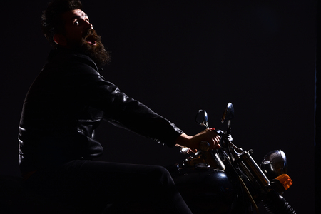 Man with beard, biker in leather jacket sitting on motor bike in darkness, black background. Bikers leisure concept. Macho, brutal biker in leather jacket riding motorcycle at night time, copy space