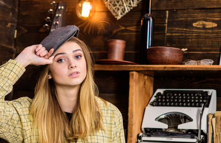 Girl in casual outfit with kepi in wooden vintage interior. Girl tomboy spend time in house of gamekeeper. Lady on calm face in plaid clothes looks cute and casual. Tomboy concept