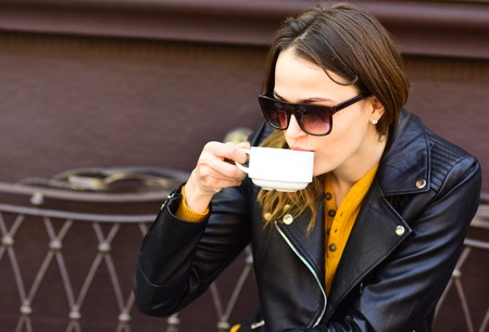 Girl in sunglasses drinks tasty coffee on brown terrace background