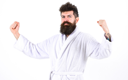 Health and fitness concept. Bearded guy in bathrobe showing muscles over white background. Full of energy man in the morning