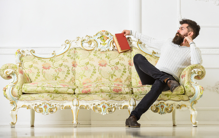 Man with beard and mustache spends leisure with book. Scientist, professor on strict face analyzing literature. Lecturer sit on sofa and holds book, white wall background. Self education concept