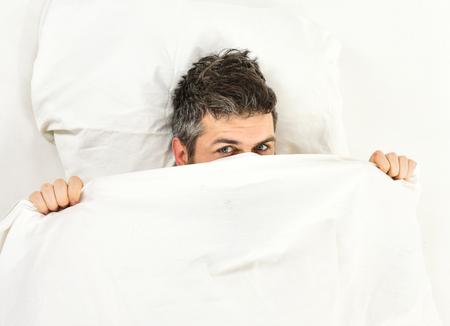 Sleepyhead concept. Man with sleepy face lies on pillow Stock Photo