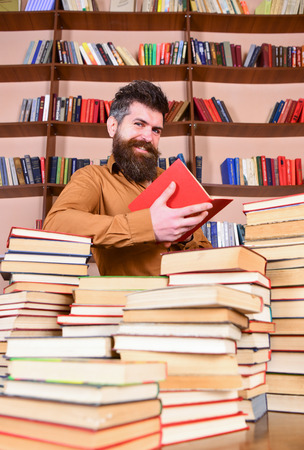 Education and science concept. Teacher or student with beard studying in library between piles of books. Man on smiling face reading book, bookshelves on background