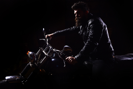 Man with beard, biker in leather jacket sitting on motor bike in darkness, black background. Night racer concept. Macho, brutal biker in leather jacket riding motorcycle at night time, copy space