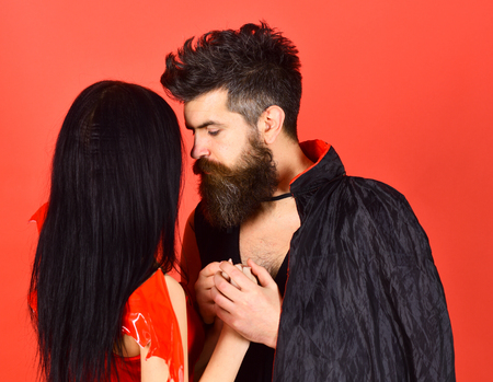 Vampire in cloak and sexy devil girl holds hands. Couple in love, perfect match. Man and woman dressed like vampire, demon, red background. Halloween concept. Couple on pensive faces play role game 스톡 콘텐츠