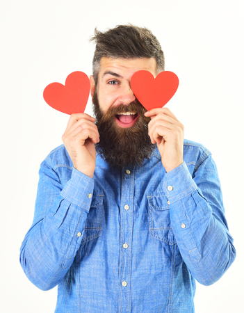 Man with beard in love holds red hearts, covers eye. Stock Photo