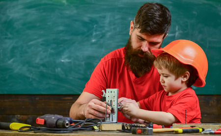 Mens work concept. Boy, child in protective helmet makes by hand, repairing, does crafts with dad. Father with beard and little son in classroom teaching to use tools, chalkboard on background