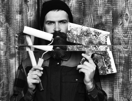 bearded builder man holding various building tools with serious face 스톡 콘텐츠