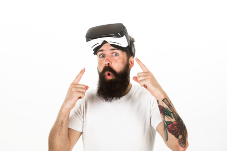 Man with beard and mustache holds VR glasses, white background. VR technology concept. Guy with VR glasses or head mounted display. Hipster on excited face pointing at gadget with index finger
