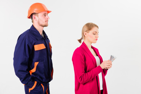 Builder looks at woman with busy face counting money, Stock Photo