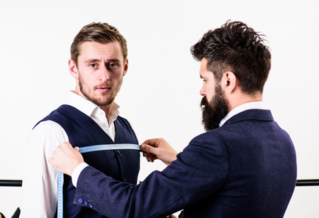 Businessman, client stand near hanger with suits while tailor working. Stock Photo