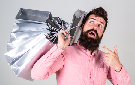 Sale and discount concept. Guy shopping on sales season, pointing at bags. Hipster on surprised face addicted shopaholic. Man with beard and mustache carries bunch of shopping bags, grey background