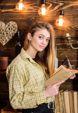 Poetry evening concept. Girl in casual outfit in wooden vintage interior enjoy poetry. Girl reading poetry in warm atmosphere. Lady on dreamy face in plaid clothes holds book, reading poetry Archivio Fotografico