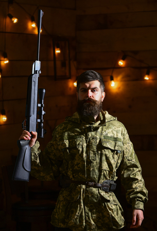 Gamekeeper concept. Man with beard wears camouflage clothing in wooden interior background. Macho on strict face at gamekeepers house. Hunter, brutal hipster with gun in his hand ready for hunting