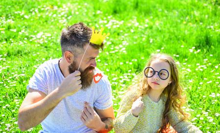 Dad and daughter sits on grass at grassplot, green background. Family spend leisure outdoors. Child and father posing with crown and eyeglasses photo booth attributes. Best friends concept