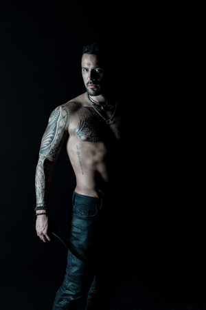 Athlete or sportsman with muscular chest and belly. Tattoo model with six pack and ab. Bearded man with tattooed body. Man with sexy bare torso in jeans. Sport or fitness and bodycare.