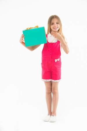 Little child point finger at shopping bag isolated on white. Happy girl smile with paper bag. Kid shopper in fashion jumpsuit. Holidays and celebration. Shopping at black friday. All I got on sale