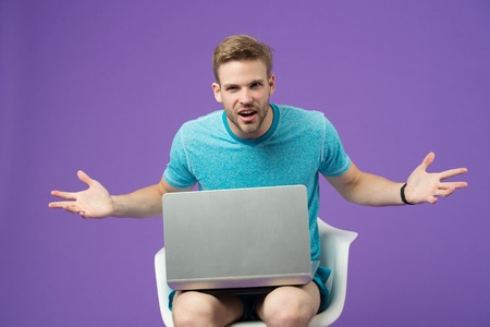 Angry man with laptop on violet background. Man in blue tshirt with computer on purple background. Internet surfing and virtual world. Blog or blogging and weblog. Modern life in social network.