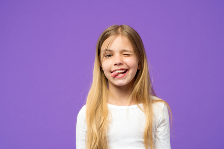 Little girl show tongue. Child with funny face on violet background. Cute kid with beauty look and long blond hair. Beauty look and hair care. Happy childhood and childcare, copy space. Stock Photo