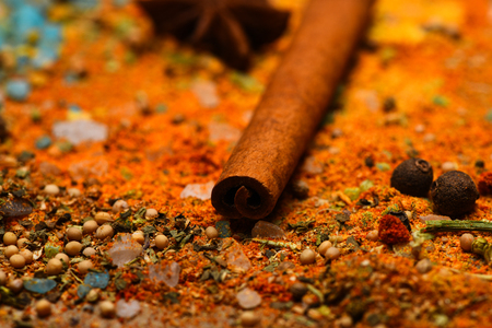 Condiments concept. Spices and ingredients on wooden texture. Cinnamon stick, star anise, red grinded pepper and curcuma on wooden background, close up. Condiments scattered all over surface