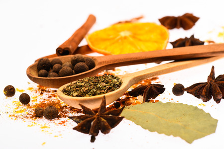 Spices kit concept. Spices kit for cooking or preparing hot drinks, close up. Spices mix with kitchen herbs and dried ingredients. Spoons, dried orange and cinnamon stick on white background