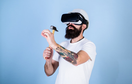 Builder and renovation concept. Man with beard in VR glasses holds hammer, light blue background. Guy with HMD hammering virtual nail into VR surface. Hipster busy with renovation in virtual reality