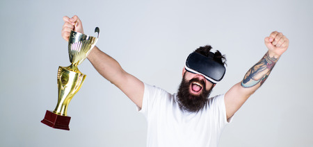 Hipster on happy face squeezing fist as successful gesture. Guy with head mounted display won in virtual game. Man with beard in virtual reality glasses holds goblet, light background. Winner concept
