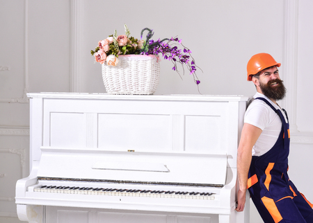 Courier delivers furniture, move out, relocation. Man with beard worker in helmet and overalls pushes, put efforts to move piano, white background. Heavy loads concept. Loader moves piano instrument