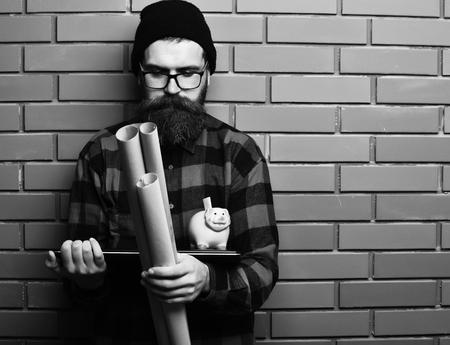 Bearded caucasian hipster holding laptop, piggy bank and craft paper 免版税图像
