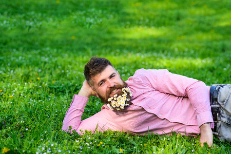 Man with beard on smiling face enjoy nature. Masculinity concept. Hipster with daisies in beard looks attractive. Bearded man with daisy flowers lay on meadow, lean on hand, grass background 版權商用圖片
