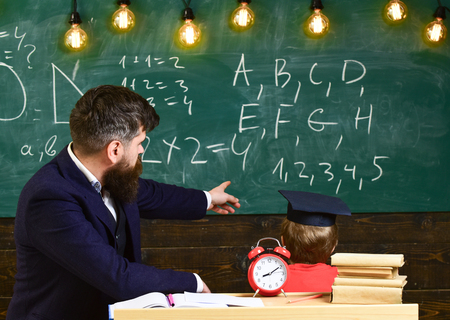 Boy, child in graduate cap looks at scribbles on chalkboard while teacher explains. Teacher with beard, father teaches little son in classroom, chalkboard on background. Individual lesson concept