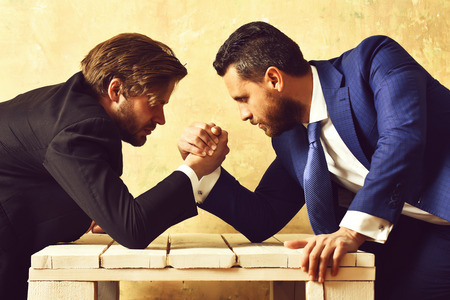 Boss and employee arm wrestling in office Foto de archivo