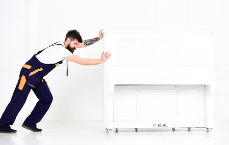 Man with beard and mustache, worker in overalls pushes piano, white background. Loader moves piano instrument. Courier delivers furniture in case of move out, relocation. Courier service concept Standard-Bild