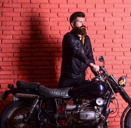Hipster, brutal biker on serious face in leather jacket gets on motorcycle. Start of journey concept. Man with beard, biker in leather jacket near motor bike in garage, brick wall background