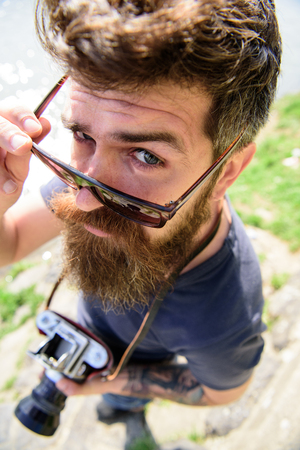 Hipster on strict face holds old fashioned camera. Tourist photographer concept. Guy shooting nature near river or pond. Man with beard and mustache puts on sunglasses, water surface on background