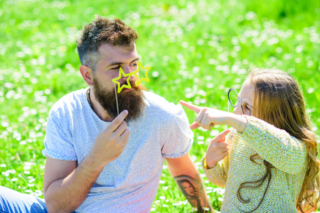 Communication concept. Dad and daughter sits on grass at grassplot, green background. Family spend leisure outdoors. Child and father posing with eyeglases photo booth attribute while speaking